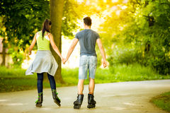 Couple ride rollerblades in the park Royalty Free Stock Photo