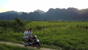 Couple rides scooter among fields against mountains aerial stock footage