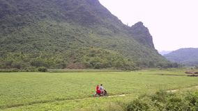 Couple rides small motorcycle along narrow ground road