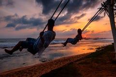 Couple rides on swings on sunset stock image