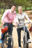 Couple riding bicycle in park. Smiling and looking forward royalty free stock images