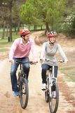 Couple riding bicycle in park Stock Photo