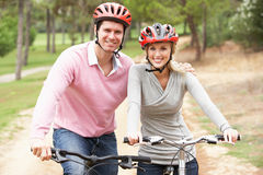 Couple riding bicycle in park Stock Images