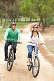 Couple riding bicycle in park Royalty Free Stock Photos