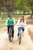 Couple riding bicycle in park. Looking at eachother smiling royalty free stock photos