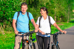 Couple riding a bicycle in a park Stock Photos