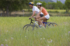 Couple riding bicycle through rural field royalty free stock images
