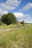 Couple riding bicycles on countryside path stock photography