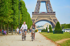 Couple riding bicycles near the Eiffel tower in Paris Royalty Free Stock Photo