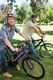 Couple riding bicycles in parkland Royalty Free Stock Images
