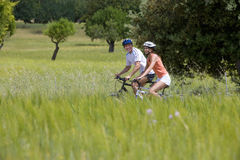Couple riding bicycles through rural field stock photo