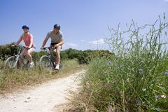 Couple riding bicycles on rural path Stock Images
