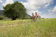 Couple riding bicycles on rural path Royalty Free Stock Images