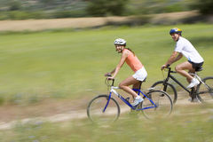 Couple riding bicycles on rural path stock photos