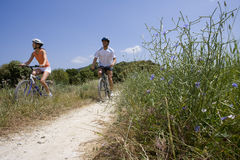 Couple riding bicycles on rural path Stock Photo