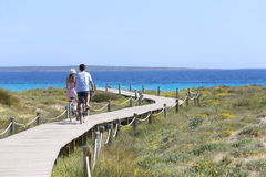 Couple riding bicycles on a wooden path towards the sea Stock Image