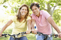 Couple riding bikes Stock Photos