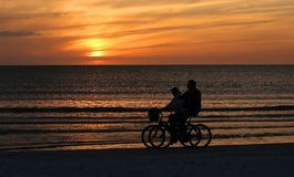 Couple riding bikes on the beach at sunset. Couple ride side by side enjoying the sunset and getting their exercise on beautiful Fort Myers Beach, Florida, USA Stock Images