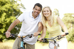 Couple riding bikes in countryside Royalty Free Stock Images