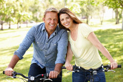 Couple riding bikes in park stock photos