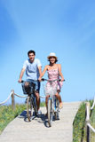 Couple riding bikes on a wooden pontoon. Couple riding bicycles in summertime Royalty Free Stock Images