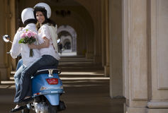 Couple riding on blue motor scooter near colonnade, woman holding bouquet of flowers, looking over shoulder, smiling, rear view, p Stock Photography