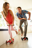 Couple Riding Childrens Scooters Indoors Stock Photos