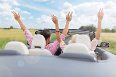 Couple riding in convertible with arms overhead Stock Image