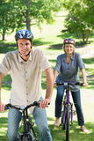 Couple riding cycles in park Royalty Free Stock Image