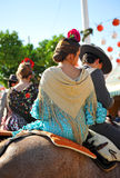 Couple riding at horse in the Seville Fair, feast in Spain Stock Images