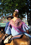 Couple riding at horse in the Seville Fair, feast in Spain Stock Image