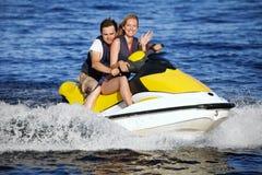 Couple riding jet ski Stock Photos