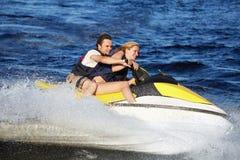 Couple riding jet ski. Happy smiling caucasian couple riding jet ski Royalty Free Stock Image