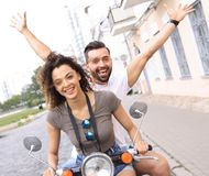 Couple riding motor scooter in old city street. Beautiful young couple is smiling while riding a scooter Royalty Free Stock Images
