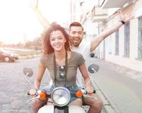 Couple riding motor scooter in old city street. Beautiful young couple is smiling while riding a scooter Royalty Free Stock Photo