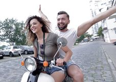 Couple riding motor scooter in old city street. Beautiful young couple is smiling while riding a scooter Royalty Free Stock Photography