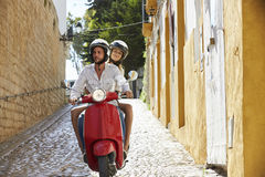 Couple riding motor scooter in old Ibiza street, front view Royalty Free Stock Photography