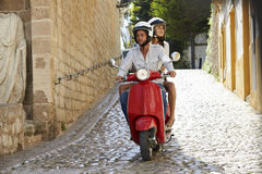 Couple riding motor scooter in old Ibiza street, full length Stock Photos