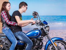 Couple Riding a Motorbike with Beach Background. Young Sweet Couple in Trendy Outfits Riding a Blue Motorbike with Tranquil Beach Background Royalty Free Stock Photos