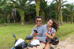 Couple Riding Motorbike, Young Man And Woman Using Cell Smart Phone Travel On Bike On Tropical Forest Road Royalty Free Stock Image