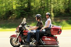 Couple riding motorcycle. This is a men and smiling women enjoying an afternoon ride on their motorcycle wearing helmets royalty free stock photo