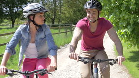 Couple Riding Mountain Bikes Along Country Track