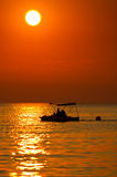 Couple riding a pedal boat on the sea at sunset Stock Photos