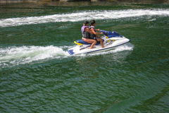 Couple riding a personal watercraft Stock Image
