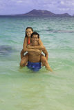 Couple riding piggyback in the ocean Royalty Free Stock Image