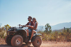 Couple riding on a quad bike. Young men and women riding on a quad bike. Couple on holiday enjoying on a ATV bike ride on a summer day Royalty Free Stock Images
