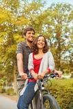 Couple riding on a same bike. Happy couple riding on a same bike Royalty Free Stock Photography