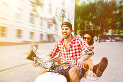 Couple riding a scooter in the city Stock Image