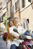 Couple Riding Scooter On Street Royalty Free Stock Photography