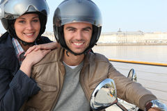 Couple riding scooter together Royalty Free Stock Image